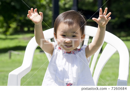 An infant sitting in a chair and waving a hand 7260684
