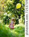Little baby girl with a yellow balloon 7293709
