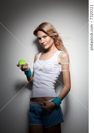 Portrait of young smiling woman with tennis ball 7320221