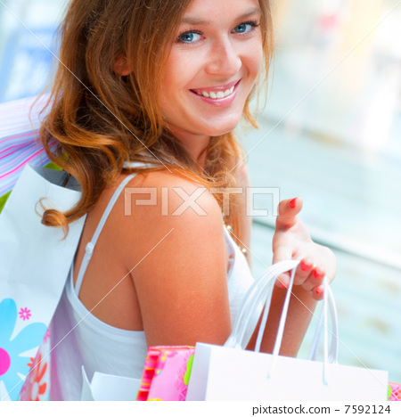Happy shopping woman at the mall preparing gifts for her friends 7592124