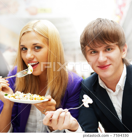 Closeup portrait of an attractive young couple eating fruit sala 7594330