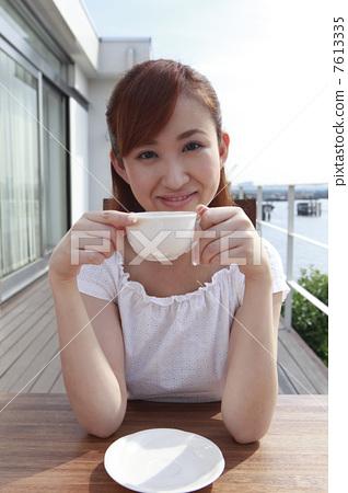 一個在露台上喝茶的女人 7613335
