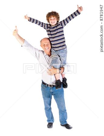 Grandfather giving grandson piggy-back 8781947