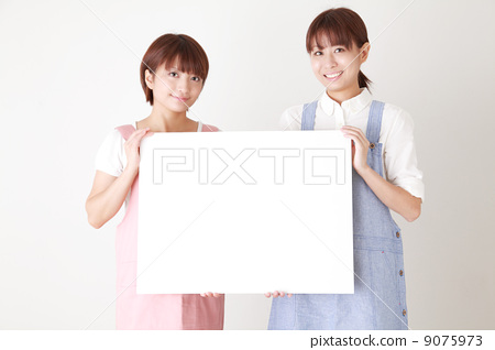 Two women in an apron with a board 9075973