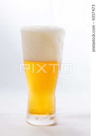 Foam spilling from glass beer edge flowing 9357473
