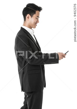 distracted asian businessman using phone while walking 9402376