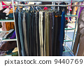 different group colored jeans hanging on a hanger in store 9440769