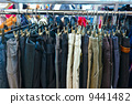 group of different colored jeans hanging on a hanger in store 9441482