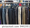 group different colored jeans hanging on a hanger in store 9441991