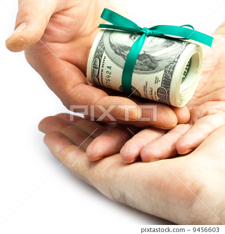 Dollars rolled into a tube tied with ribbon in the hands 9456603