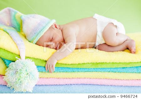 newborn baby girl sleeping on color towels 9466724