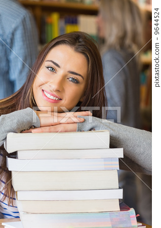 Stock Photo: Female student with stack of books while others in background at