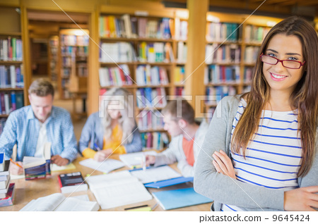 Stock Photo: Female student with others in background at library