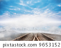 Train tracks leading to city on the horizon 9653152