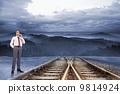 Composite image of thinking businessman holding glasses 9814924