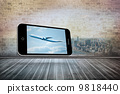 Composite image of airplane on smartphone screen 9818440