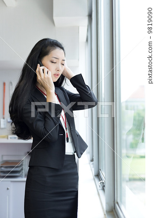 Young business woman using mobile phone outside office cubicle 9819090