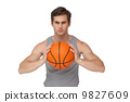 Fit man holding basketball about to throw 9827609