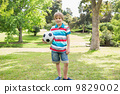 Portrait of a smiling boy with ball at park 9829002