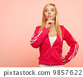 Secret woman. Fitness girl showing hand silence sign 9857622