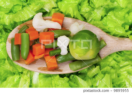Vegetables on wooden spoon on lettuce 9895955