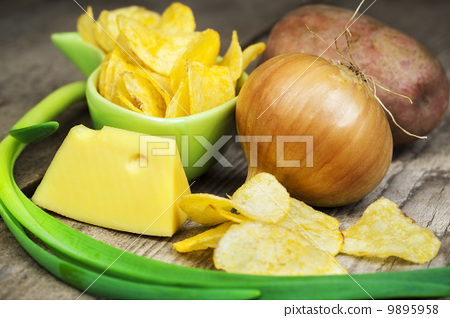 Crispy chips in green bowl on wooden boards 9895958
