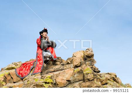 man in Mongolian costume on rock 9915121