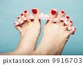 foot pedicure applying red toenails on blue 9916703