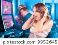 Friends gambling on slot machine 9952645