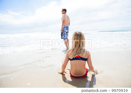 Young girl sitting on sand at beach watching father 9970919
