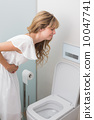 Woman with stomach sickness about to vomit into toilet 10047741