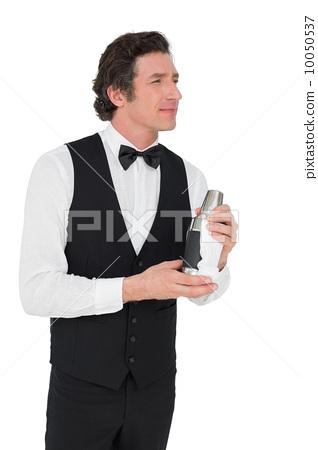 Thoughtful bartender holding cocktail shaker 10050537