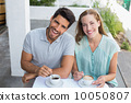 Happy young couple with coffee cups at café 10050807
