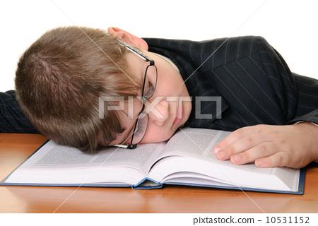 Boy in glasses sleeps on book 10531152