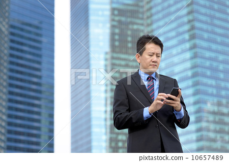 Successful entrepreneur business man using mobile phone in front of glass office building 10657489