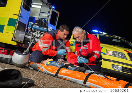 Stock Photo: Paramedics giving firstaid to motorbike driver
