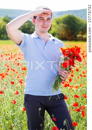 Young man with bouquet of poppies 10778782