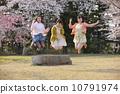 벚꽃 나무 아래에서 점프하는 세 명의 젊은 여성 10791974