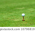 Golf ball on a tee against the golf course with copy space 10796819