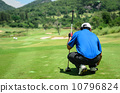 golf player with putter squatting to analyze the green at golf c 10796824