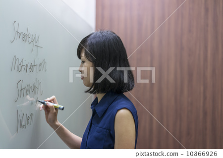 A young chinese female executive preparing presentation on a white board 10866926
