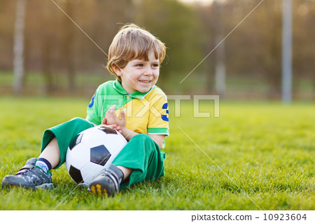 Blond boy of 4 playing soccer with football on football field 10923604