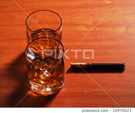 Highball whiskey glass with ice and cigar on wooden background. 10976021