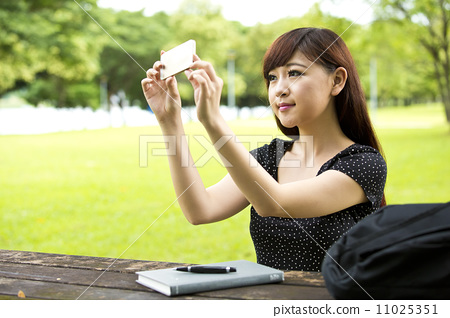 Beautiful young teenage female student looking at phone doing selfie photo 11025351