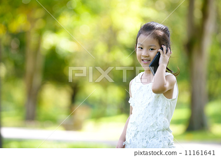 Little girl in casual using mobile smart phone in a park 11161641