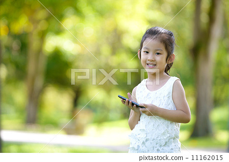 Cute little girl in causal holding mobile smart phone in a park 11162015