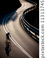 Cyclist riding along a mountain road 11313745
