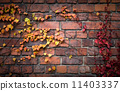 Detailed brick wall background texture with red and yellow autumnal leaves on it 11403337