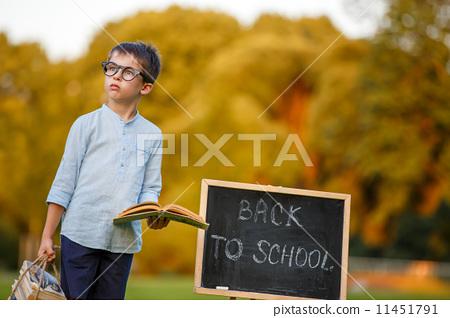 Cute little schoolboy reading book 11451791