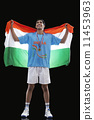 Happy young hockey medalist with Indian flag standing against black background 11453963